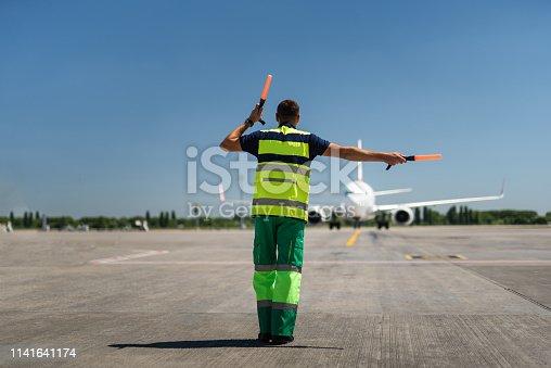Time for landing. Aviation marshaller meeting passenger plane at the airport