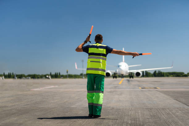 Air traffic controller signaling Time for landing. Aviation marshaller meeting passenger plane at the airport cabin crew stock pictures, royalty-free photos & images