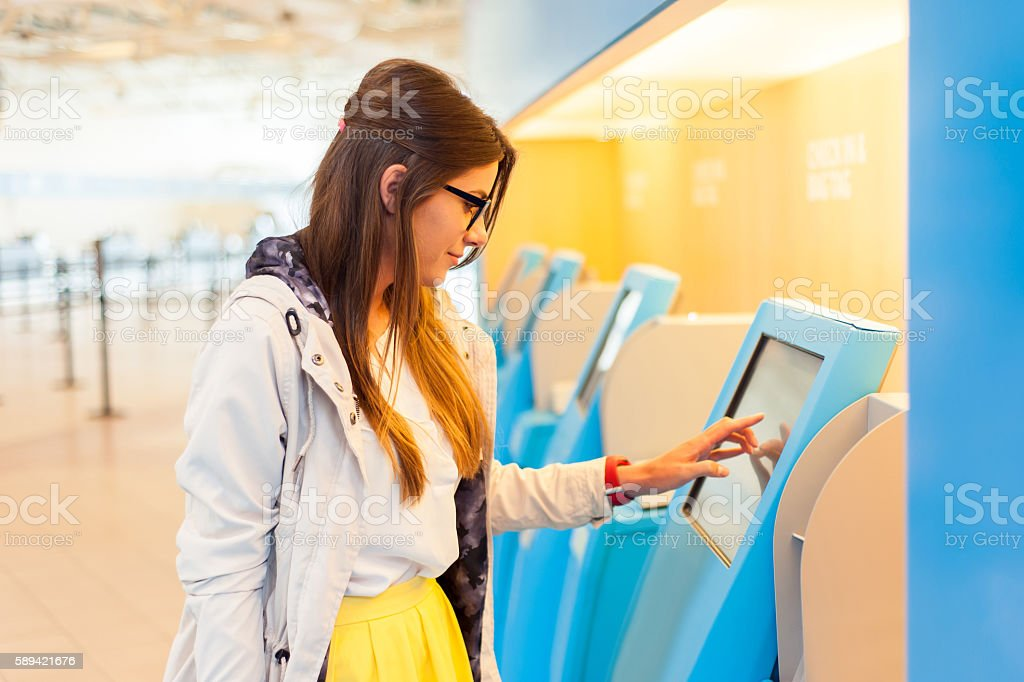 Air travel concept. The check in process. Young woman at self service transfer area doing self-check-in at automated machine with touchscreen display in airport terminal building Adult Stock Photo