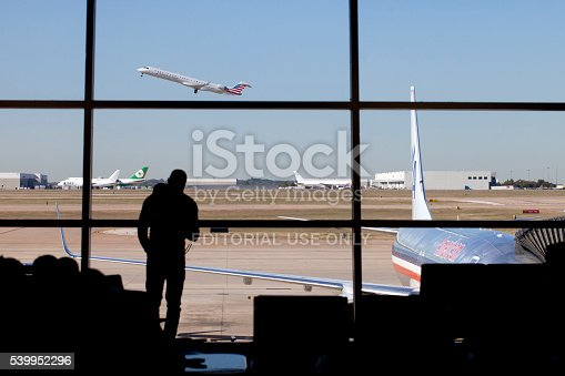Dallas, Texas, USA - November 12, 2015: Silhouette of man standing infront of window watching an airplane take off at Dallas - Fort Worth (DFW) airport in Texas,