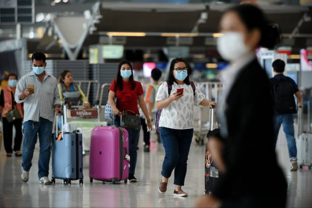 Air Travelers Wear Masks as a Precaution against Covid-19 Bangkok, Thailand - February 18, 2020: Air travelers wearing masks walk through departures hall of Suvarnabhumi Airport. Thailand has been assessed as a country at risk of Covid-19 outside of China. airport stock pictures, royalty-free photos & images
