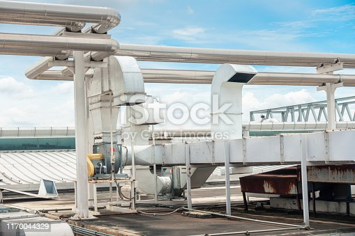 1071156490 istock photo Air Ventilation Exhausting Blower and Chiller Pipe on Roofing Floor of Manufacturing Power Plant. Building Structure of Air Conditioning Chiller Pipeline and Outlet Vent Duct Hood for HVAC System 1170044329