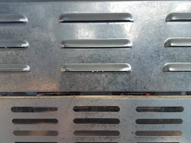 air vents on back of dirty barbecue grill stock photo