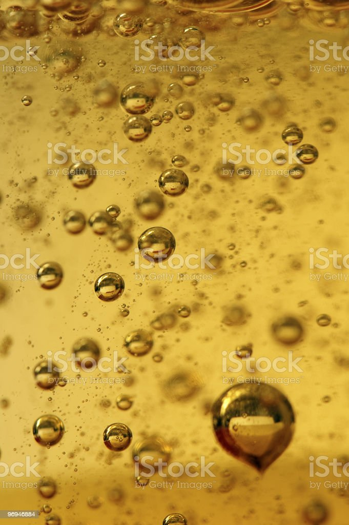 Air vials in a golden liquid royalty-free stock photo