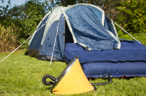 A footpump inserted into a camping airbed ready for inflation - focus on the pump.Related images in my portfolio: