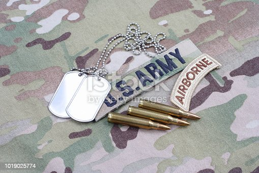 istock US ARMY airborne tab, flag patch,  with dog tag and 5.56 mm rounds on camouflage uniform 1019025774