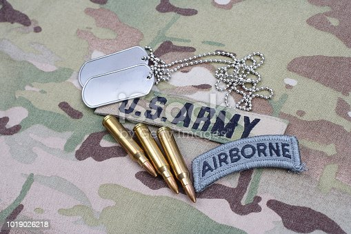 istock US ARMY airborne tab, flag patch,  with dog tag and 5.56 mm rounds on camouflage uniform 1019026218