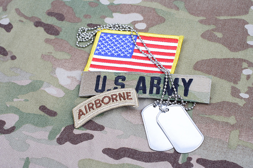 istock US ARMY airborne tab, flag patch,  with dog tag on camouflage uniform 1019026246