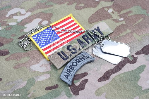 istock US ARMY airborne tab, flag patch,  with dog tag on camouflage uniform 1019028480
