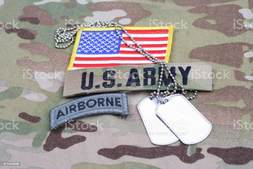 US ARMY airborne tab, flag patch, with dog tag on camouflage uniform stock photo
