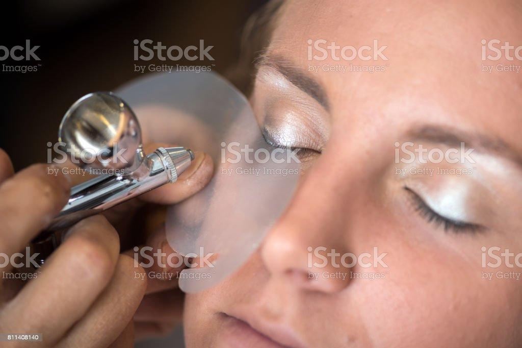 Airbrush makeup and hairdressing salon: Applying makeup stock photo