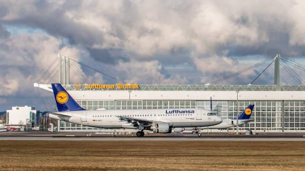 airbus a320 lufthansa landet vor dem lufthansa technik gebäude am flughafen münchen - andreas haas stock-fotos und bilder