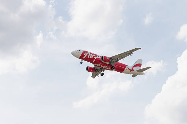 airbus a320-216 of indonesia airasia landing to don mueang airport - aviation and environment summit stock photos and pictures