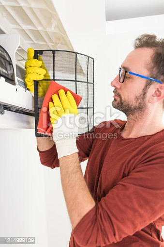 931591820 istock photo Aircondition service and maintenance, fixing AC unit and cleaning / disinfecting the filters from dangerous pathogens. 1214999139
