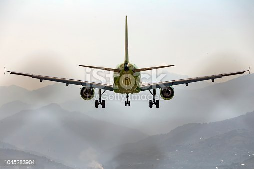 864534880 istock photo Aircraft, airliner with landing gear comes to land on the background of the mountains. Rear view. 1045283904