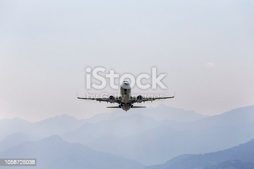 864534880 istock photo Aircraft, airliner with landing gear comes to land on the background of the mountains. Rear view. 1058725038