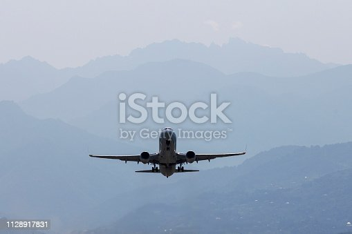 864534880 istock photo Aircraft, airliner with landing gear comes to land on the background of the mountains. Rear view. 1128917831