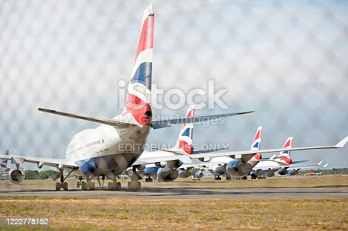 Boeing 747-400 series aircraft, Bournemouth Hurn Airport, Dorset, England, UK. Redundant British Airways Jumbo Jets parked on the perimeter track of Bournemouth Hurn Airport, seen through chain-link fencing during Coronavirus lockdown, when the virus grounded all international aircraft and travel.