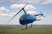 The aircraft - the small Blue Helicopter flight sky and clouds background.