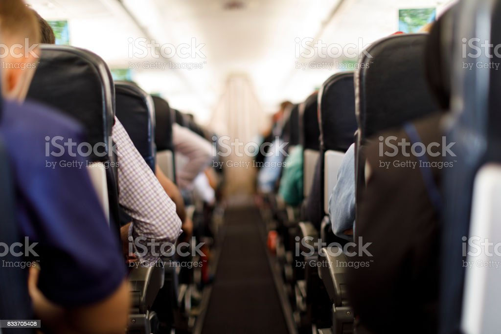 Aircraft cabin with passengers stock photo