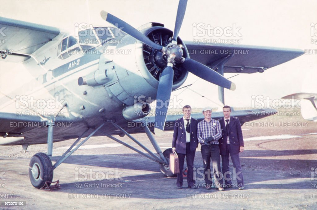 Aircraft crew against Antonov AN-2 at Ust-Ilimsk Airport, 80's. stock photo