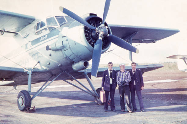 Aircraft crew against Antonov AN-2 at Ust-Ilimsk Airport, 80's. Portrait of first and second pilots with a mechanic in Ust-Ilimsk airport against the background of an AN-2 plane by Aeroflot airline. Ust-Ilimsk, Irkutsk region, Siberia, the USSR. Summer of 1987. The original image was taken on Zenit-E 35mm SLR, lens 58mm Helios-44, ORWOChrom ISO 135 color reversal film. flight suit stock pictures, royalty-free photos & images