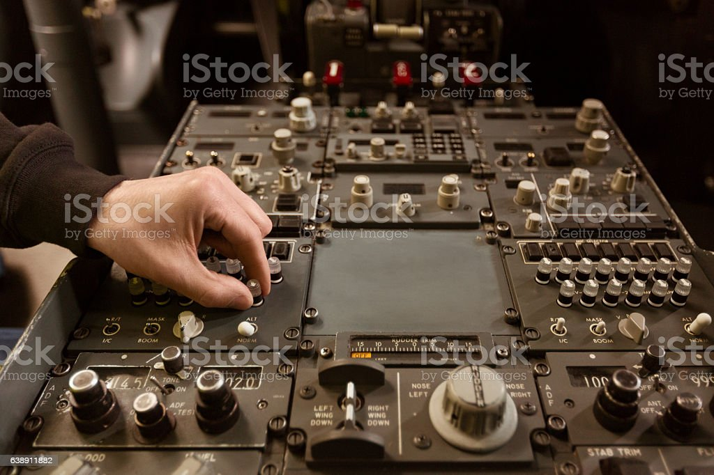 Aircraft engineer examining cockpit Aircraft engineer examining cockpit, unrecognizable person.  Adult Stock Photo
