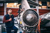 Aircraft mechanic probing an opened jet engine of an airplane with a portable camera and looking at the monitor in the maintenance hangar.