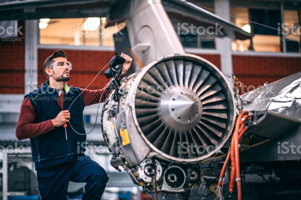 Aircraft engineer in a hangar holding a camera probe while repairing and maintaining airplane jet engine stock photo
