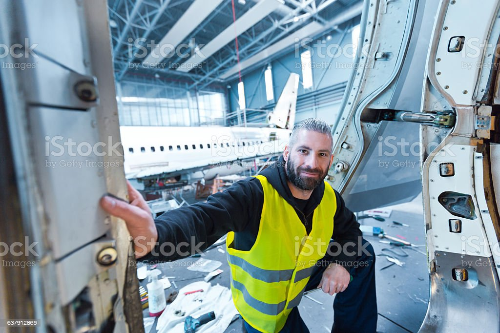 Aircraft engineer in a hangar Aircraft engineer standing in a hangar, smiling at the camera. Adult Stock Photo