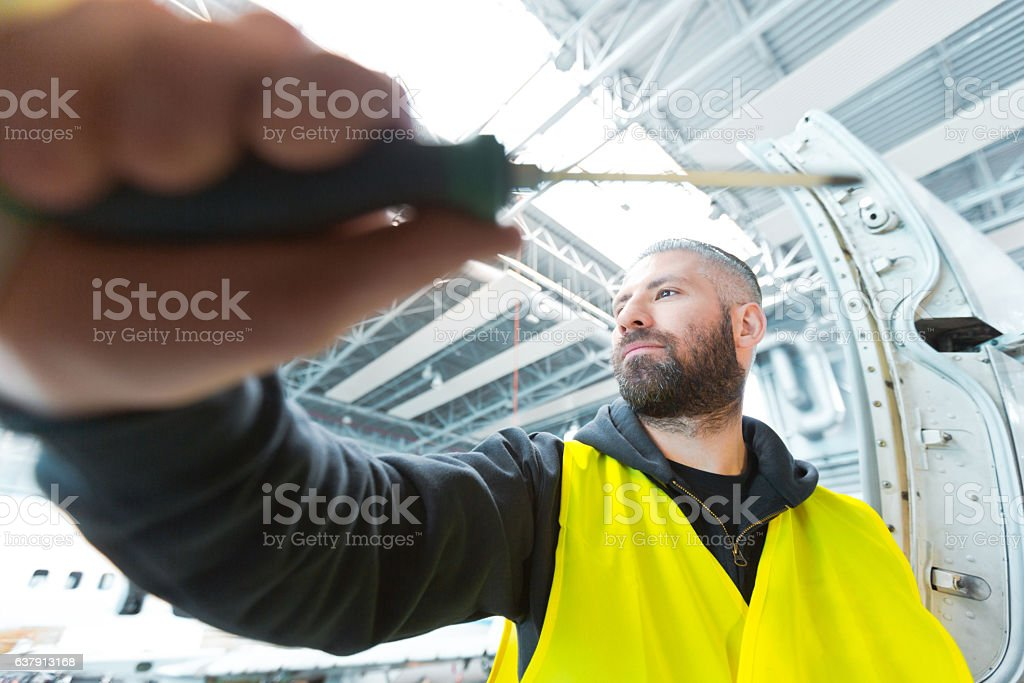 Aircraft engineer in a hangar Aircraft engineer standing in a hangar, holding screwdriver in hand. Close up oh hand. Adult Stock Photo