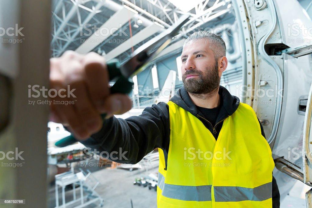 Aircraft engineer in a hangar Aircraft engineer standing in a hangar, looking away. Adult Stock Photo