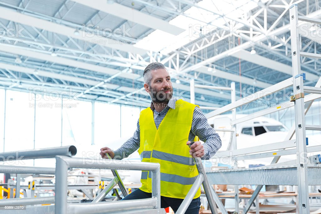 Aircraft engineer in a hangar Aircraft engineer in a hangar, airplane in the background. Adult Stock Photo