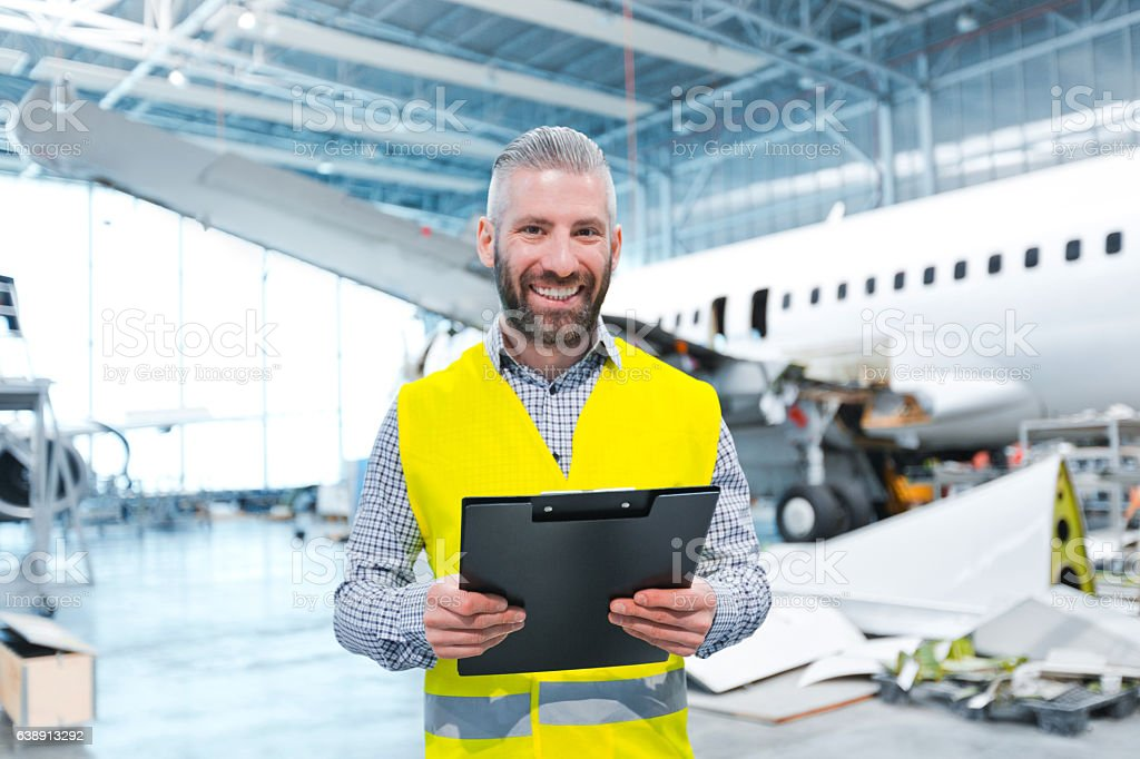Aircraft engineer in a hangar Aircraft engineer standing in a hangar, holding clipboard in hands and smiling at the camera, airplane in the background. Adult Stock Photo