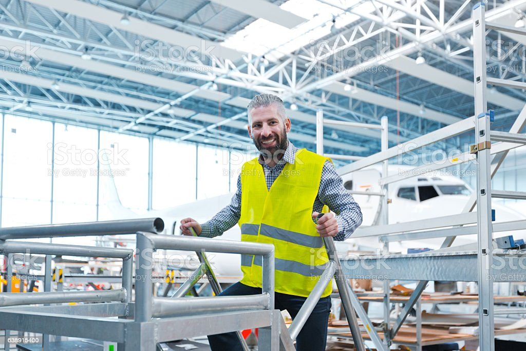 Aircraft engineer in a hangar Aircraft engineer standing in the hangar and smiling at the camera. Airplane in the background. Adult Stock Photo