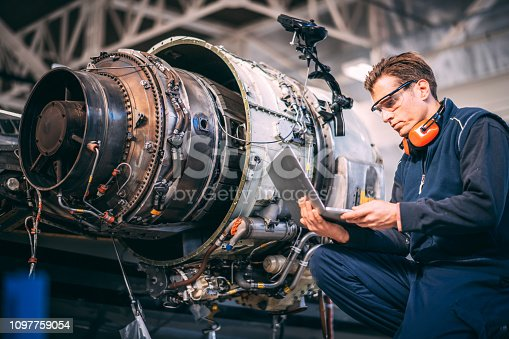 Aircraft engineer in a hangar holding laptop computer while repairing and maintaining a jet engine.