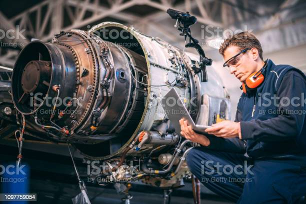 Aircraft engineer in a hangar using a laptop while repairing and an picture id1097759054?b=1&k=6&m=1097759054&s=612x612&h=ebteymv4trqud1x29ttlhiaxcaa2kuystjau4h6rqdc=