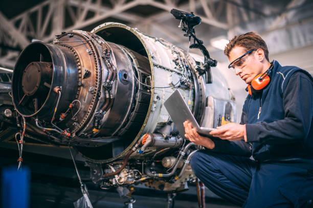 Flugzeugingenieur in einem Hangar mit einem Laptop während der Reparatur und Wartung einer Flugzeug-Jet-engine – Foto
