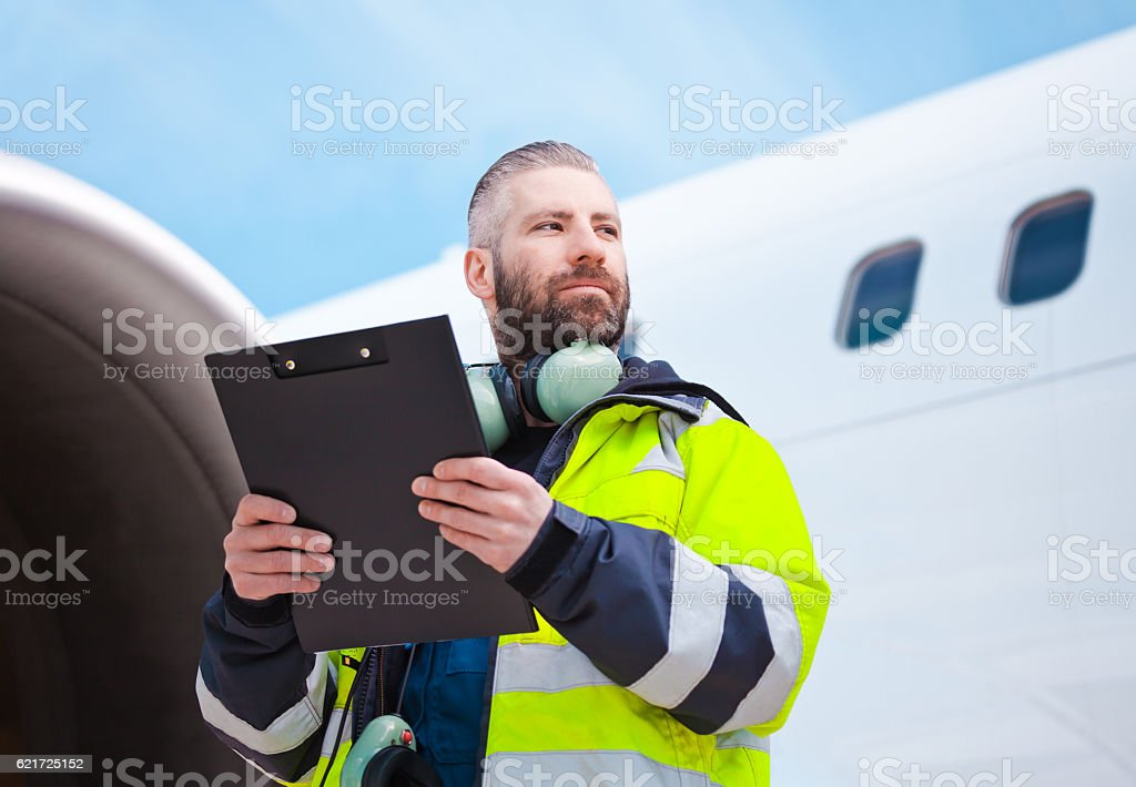 Aircraft engineer in front of airplane Aircraft engineer holding clipboard in hands standing outdoor in front of airplane. Adult Stock Photo
