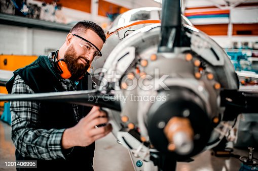 Aircraft mechanic working on a front engine assembly of a small aircraft in a hangar.