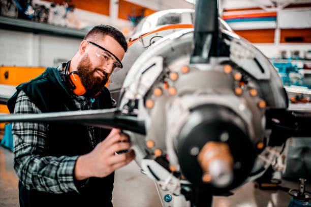 Flugzeugingenieur repariert ein kleines Fronttriebwerkflugzeug, das in einem Hangar zerlegt wurde – Foto