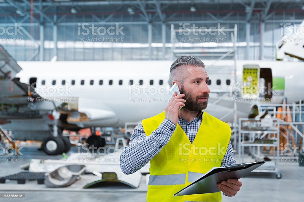 Aircraft engineer talking on mobile phone in a hangar Aircraft engineer talking on mobile phone in a hangar, holding a clipboard in hand. Adult Stock Photo