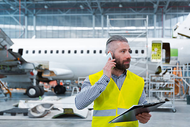 Aircraft engineer talking on mobile phone in a hangar stock photo