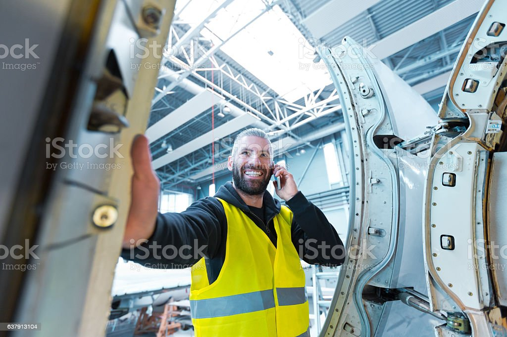 Aircraft engineer talking on smart phone in a hangar Aircraft engineer talking on smart phone in a hangar.  Adult Stock Photo