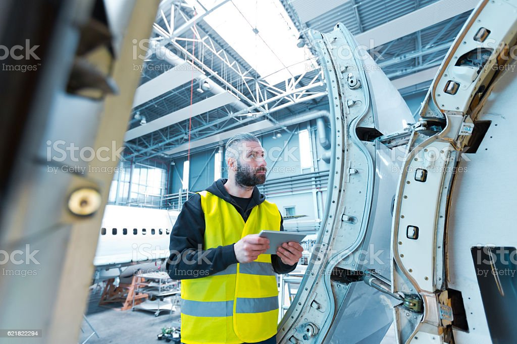 Aircraft engineer using a digital tablet in a hangar Aircraft engineer using a digital tablet in a hangar. Adult Stock Photo