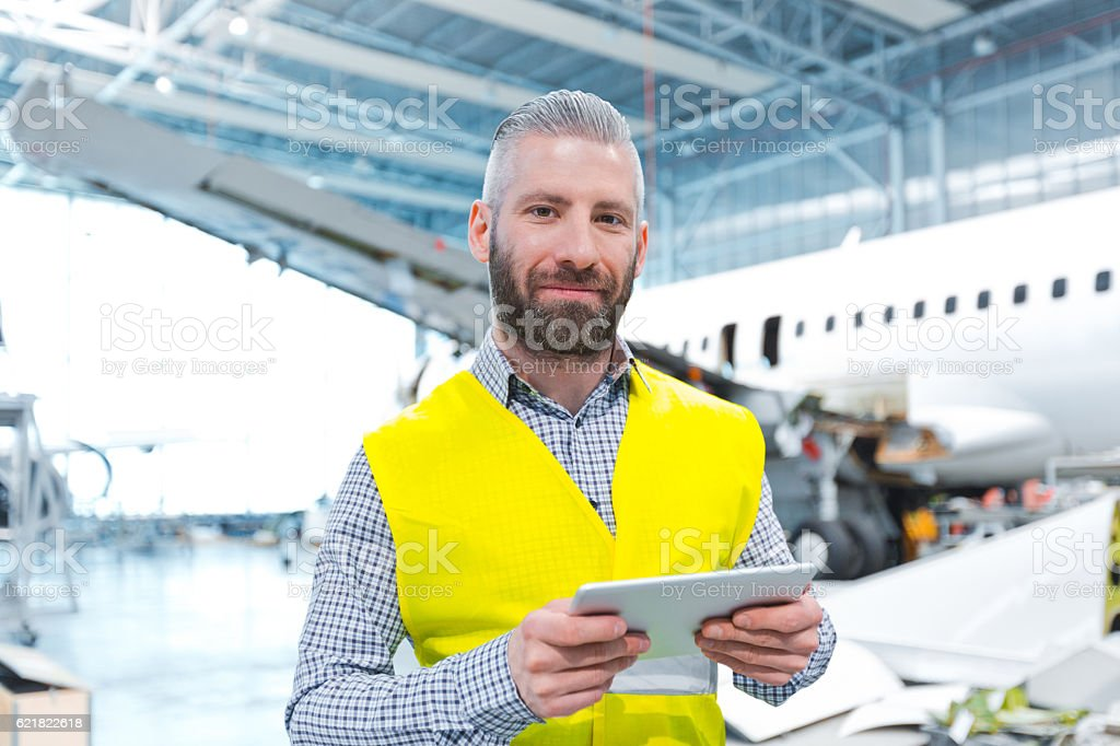 Aircraft engineer using a digital tablet in a hangar Aircraft engineer using a digital tablet in a hangar, smiling at camera. Adult Stock Photo