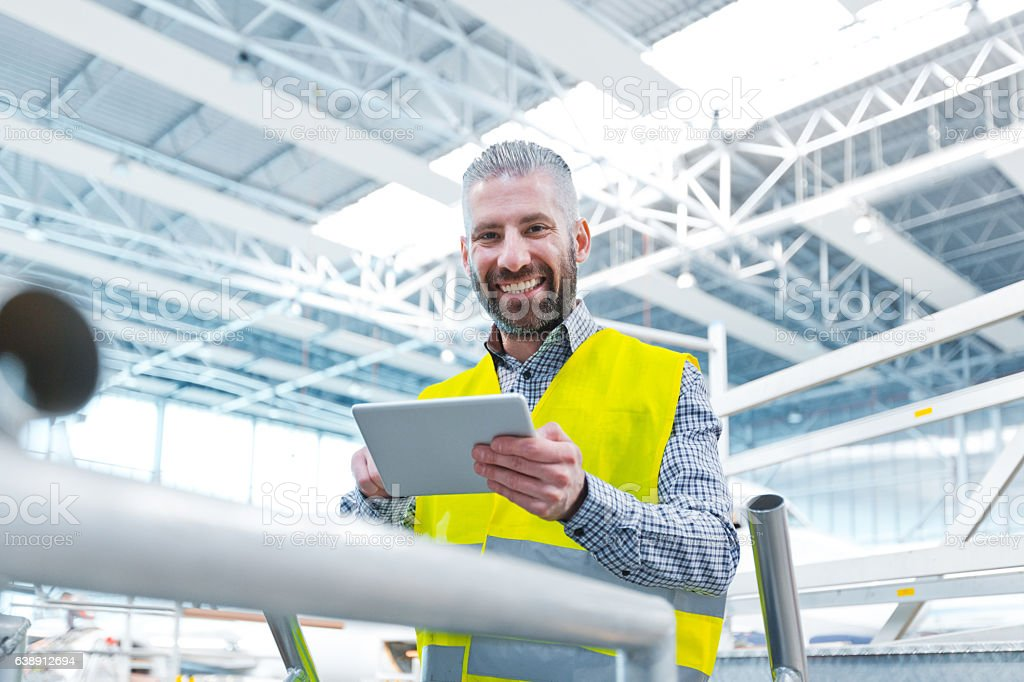 Aircraft engineer using a digital tablet in a hangar Aircraft engineer using a digital tablet in a hangar, smiling at camera, airplane in the background. Adult Stock Photo