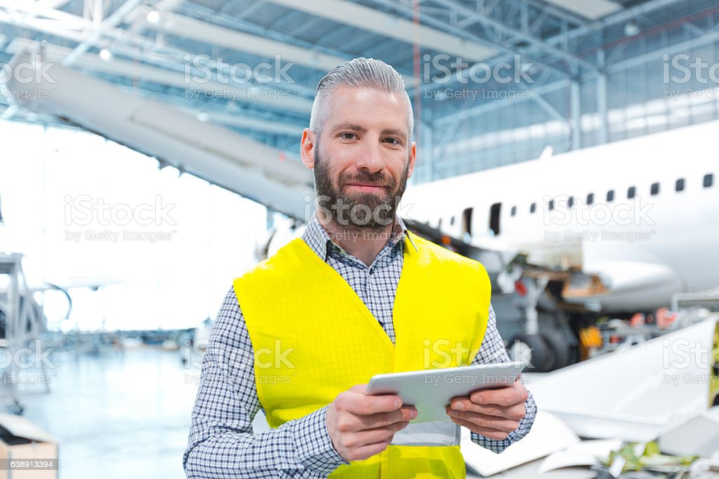 Aircraft engineer using a digital tablet in a hangar Aircraft engineer using a digital tablet in a hangar, looking at camera, airplane in the background. Adult Stock Photo