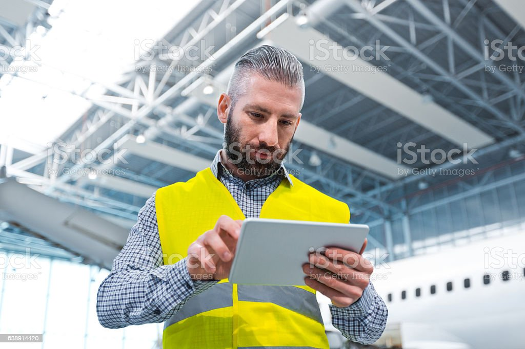 Aircraft engineer using a digital tablet in a hangar Aircraft engineer using a digital tablet in a hangar, airplane in the background. Adult Stock Photo