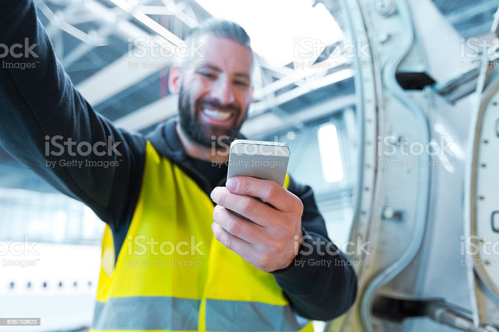 Aircraft engineer using a smart phone in a hangar Aircraft engineer using a smart phone in a hangar. Close up of hand. Adult Stock Photo